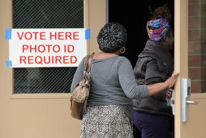 "Two women walking into a polling location with a sign on the door that says ""Vote Here Photo ID Required"""