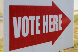 "Sign with an arrow that says ""Vote Here"""