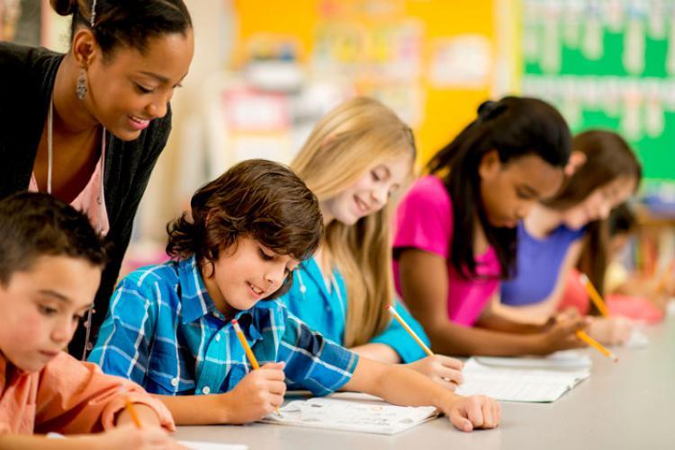 Children writing as their teacher watches over them