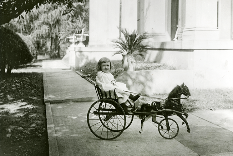 Little girl in a horse and carriage toy.