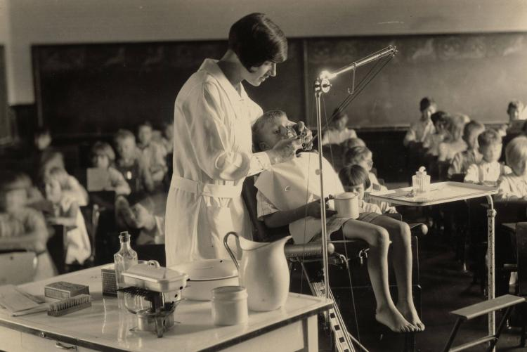 A dental hygienist cleans the teeth of a young boy during a class period circa 1924-1928.