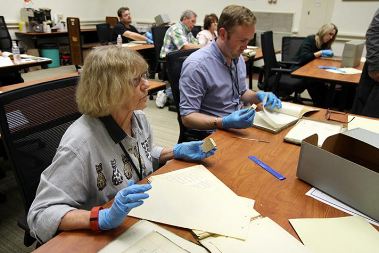 Tennessee Archives Institute participants practice cleaning historical documents.