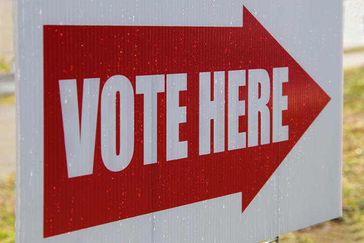 """Sign with an arrow that says """"Vote Here"""""""