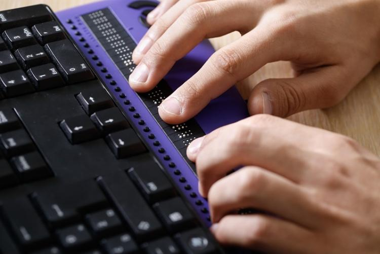 Person uses keyboard with braille display