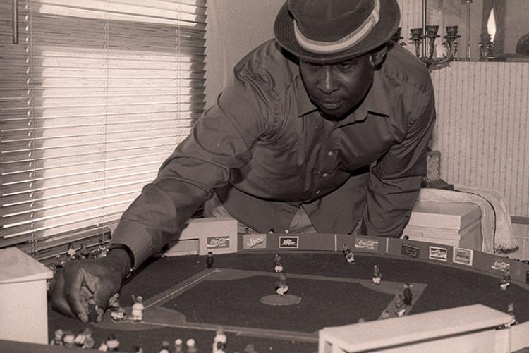 Roger Smith poses with a diorama of a baseball diamond with figures hand-carved from peach seeds, Culleoka, TN, 2001.