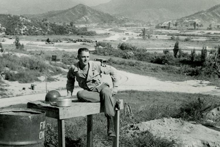 """Brock sitting on washstand at """"The Hook"""" base camp"""