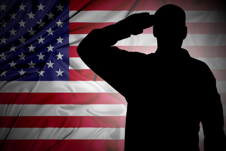 Silhouette of solider in front of the American flag